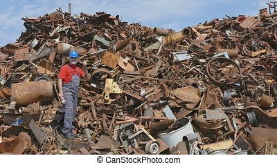 Recycling, worker at heap of metal - Metal recycling, worker...