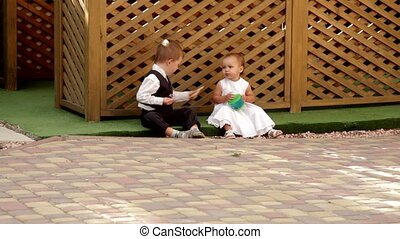 little boy and girl sitting near the gazebo and eat