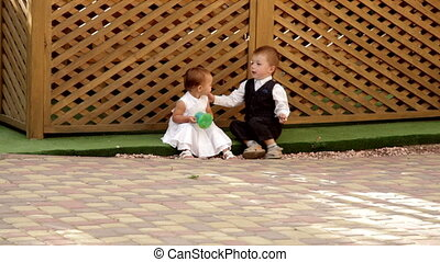 little boy and girl playing on the grass near the gazebo