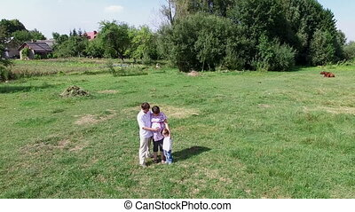 Young family walking in the summer meadow