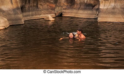 guy carries in arms girl helping swim in lake created by...