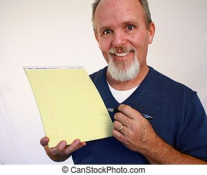 Man holding up yellow notepad with pen in hand.