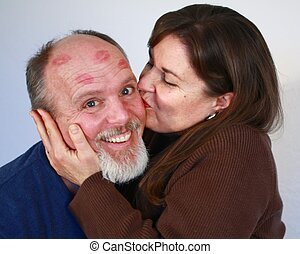 Woman with red lipsick kissing man.