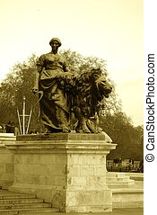 Statue - Sepia tone statue of lion and lady in front of...