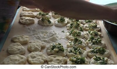 An elderly woman puts toppings on the dough