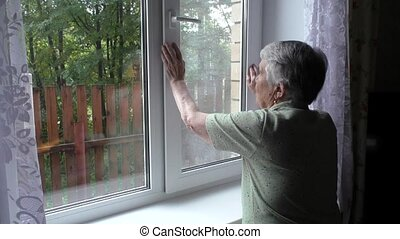 woman changes position window - An elderly woman changes...