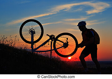 silhouette of man cyclist repairing a bike  against sunset