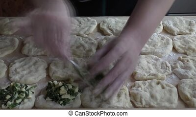 Woman puts on the dough stuffing from the egg and green...