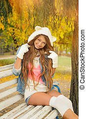 Smiling girl dressed in a cute knitted white bear hat in...