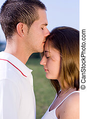 kiss - a man kissing a woman on her forehead