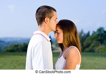 affectionate couple - a boy affectionately kissing his...