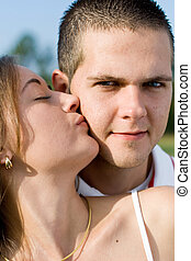love - a young woman kissing her boyfriend on the cheek