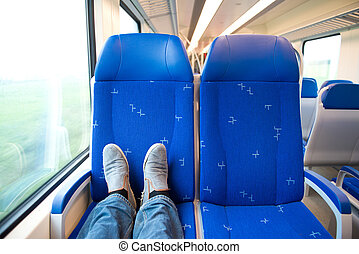 Traveling alone in a trein, feet on the seats