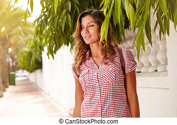 Cheerful woman looking away through green branches -...