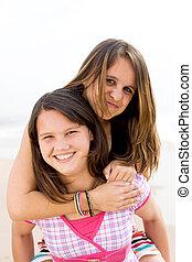 teen piggyback - a young girl giving her friend a piggyback...