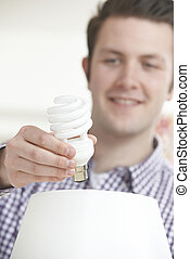 Man Putting Low Energy Lightbulb Into Lamp At Home
