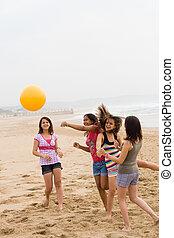 beach game - teens having fun playing with ball on beach