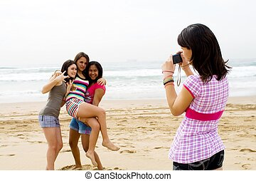 taking a photo - a teenage girl taking a photo of her three...