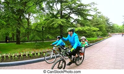 Happy Young Family Riding Bicycles In Green Park - SLOW...