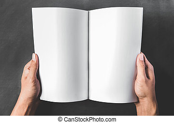 hands holding an open book with blank page - close up...