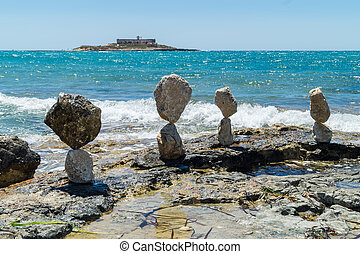 Balanced stones near island of currents in Sicily Italy