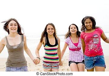 healthy teens - healthy teen girls running together on beach