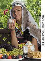 Oriental woman drinking tea at a table with fruit