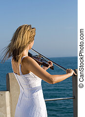 violin player - a woman playing violin on pier