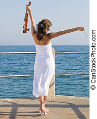 freedom - a violinist with her arms outstreched holding...