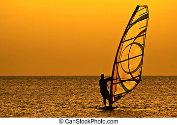 Windsurfer - Silhouette of a windsurfer in the evening sea