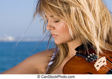 violinist - a female violinist playing with sea in...