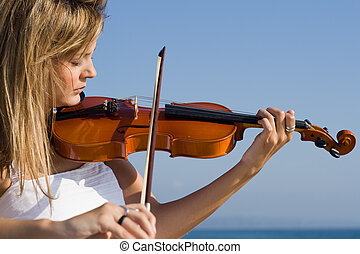 violin player - a woman in dress playing violin outdoors