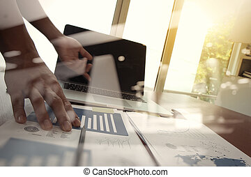 business documents on office table with laptop computer and man working in the background