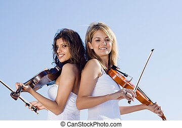 violinists - two female violin players outdoors