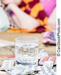 glass with medicament and pills on table close up