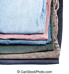 stack of different jeans and corduroys close up isolated on...