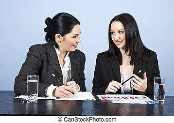 Business women conversation at meeting - Two young business...