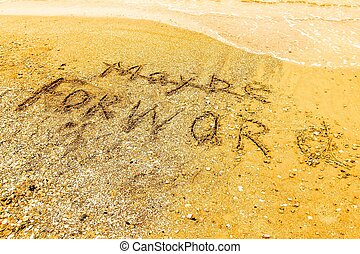 The word  FORWARD written on a sandy beach in bold.