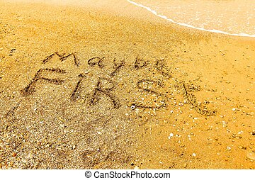 The word MAYBE FIRST written on a sandy beach in bold.