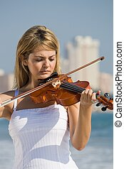female violinist - a female violinist playing with sea in...