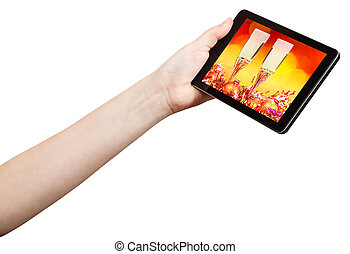 hand holds tablet-pc with Xmas still life