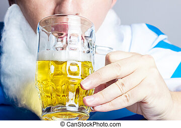 man with bavarian flag drinking glass of beer
