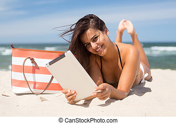 Vacations! Finally! - Young woman relaxing at the beach with...