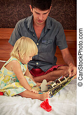 father shows childish book to little blonde daughte