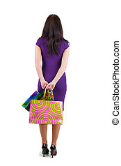beautiful woman with shoping bags looking at wall. The rear...