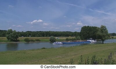 Sand barge sailing upstream on the river - wide shot - RIVER...