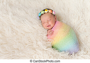Smiling Newborn Baby Girl Wearing a Rainbow Colored Swaddle...