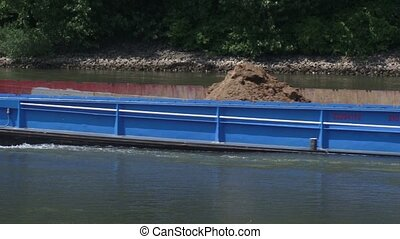 Sand barge sailing upstream on the river - close up