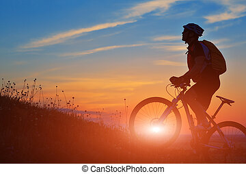Silhouette of a biker and bicycle on sky background.