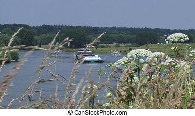 Barge sailing upstream in River landscape. Highway + moraine...
